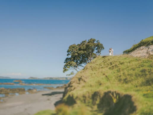 Newlyweds kiss on clifftop